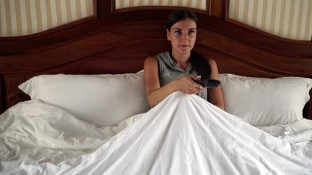 watch tv : Woman lying in bed watching television. 4k