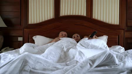 family watching tv : A married couple watching TV on the bed. A man and a woman watch TV in the evening. A young couple watching TV and bored, nothing interesting. Stock Footage