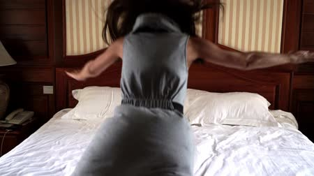 кровать : Woman falls on the bed at the hotel. 4k