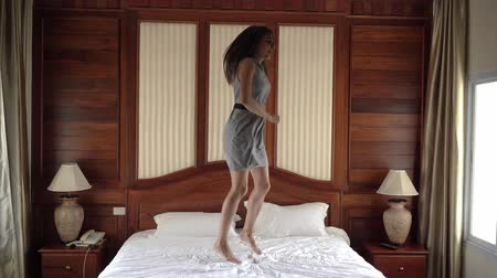 nadšení : Young beautiful woman with long hair in colorful dress dancing, jumping and spinning on the bed in bedroom with big windows. Happiness, vacation and success concept.