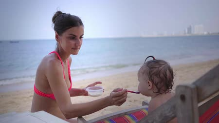 zabkása : mother feeds her daughter with a spoon on the beach. close-up. 4K Stock mozgókép
