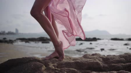 szandál : beautiful female legs in a long developing pink dress on the seashore on the stones. close-up. 4k