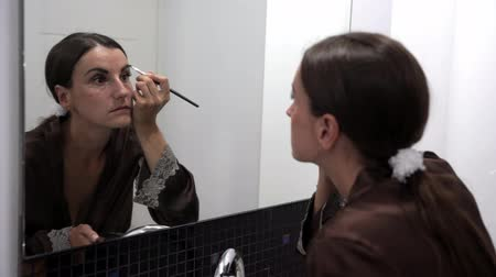 совершенство : brunette female paints her eyebrows with a brush Стоковые видеозаписи