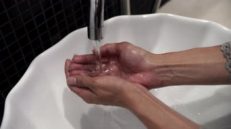 dezenfekte etmek : Female hand opens water tap and try water temperature Stok Video