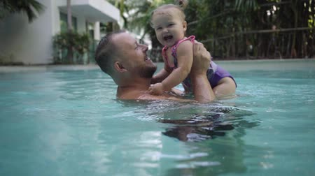 paus : Cute little kid and his father having a swimming lesson in the pool. Father holds daughter in his arms and hugs Stockvideo