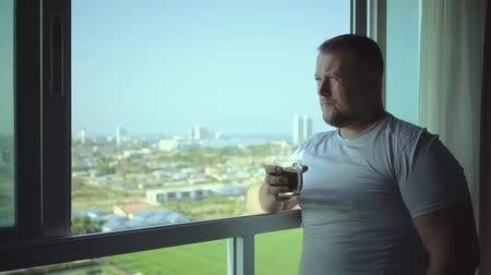 kahve molası : male drinks coffee and looks through  panoramic window smiles in the morning, slow motion. Stok Video