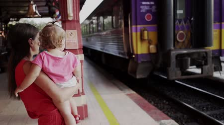 tcheco : mother and child are standing at the train station in Hua hin, Thailand, and waving to the departing train. Travel by train with a child. slow motion. Stock Footage