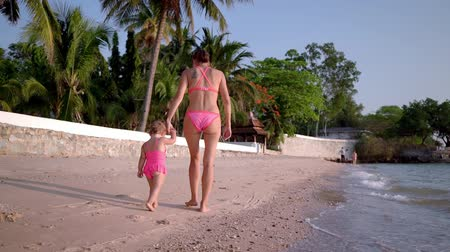 ползком : mom and little daughter in pink swimsuits walk along the seashore, rear view, slow motion Стоковые видеозаписи