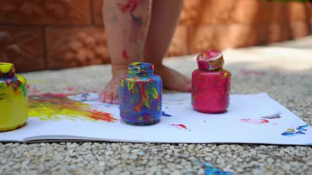 roztrhaný : child legs draws a finger paint - blue, red and yellow on a white sheet of paper. Creative child development in kindergarten or free time at home. slow motion. Dostupné videozáznamy