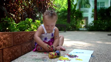 roztrhaný : Beautiful little girl draws with finger paints on a white sheet of paper. Creative child development in kindergarten or free time at home. slow motion Dostupné videozáznamy