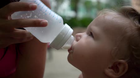 infant formula : baby girl one year old drinking bottle, tropics, slow motion