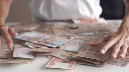 gros lot : female hands collect a lot of money on a white table, Thai banknotes, Russian banknotes Vidéos Libres De Droits