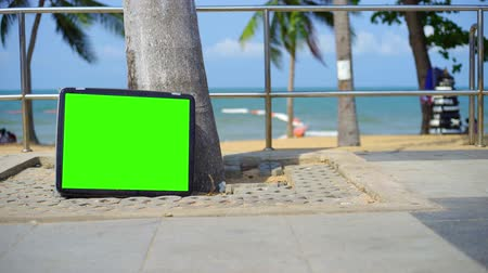 watching news : TV stands on the beach. Television with Green Screen. You can replace green screen with the footage or picture you want.