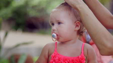 pigtailler : A woman does her hair for her little daughter by tying her hair. The concept of fashion, motherhood, beauty.