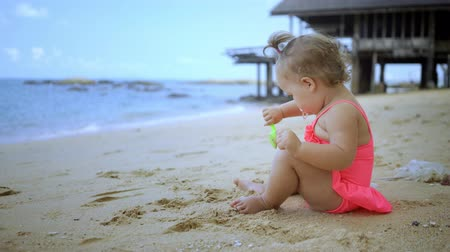 schep : little girl in a pink bathing suit playing with sand on the shore of the blue sea. concept of happy childhood, fashion, holidays