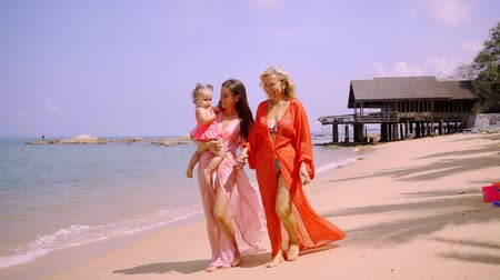 szórakoztatás : Multi generation family enjoying on the beach on a sunny day. Grandmother mother and granddaughter in pink dresses walk along the seashore. The concept of family, fashion