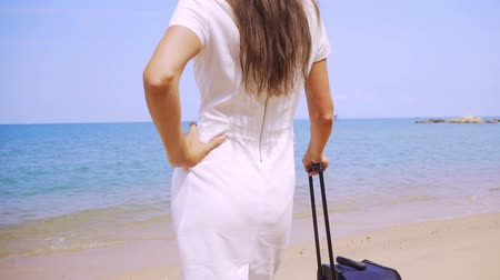 impatience : Business woman walks along the shore of a beautiful sea with a suitcase. female legs walk the shore with a suitcase freelance concept, long-awaited leisure concept Stock Footage