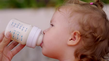 infant formula : Little beautiful girl with blue eyes drinks milk from a bottle. The child holds the bottle himself.