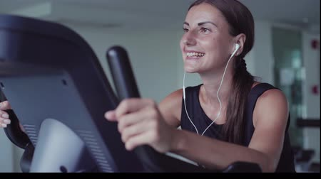 listens : Exercise bike cardio workout at fitness gym of woman taking weight loss. female listens to music on headphones. Athlete builder muscles lifestyle Stock Footage