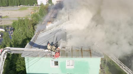çöküş : Nizhnevartovsk, Russia - July 1, 2019: firefighters extinguish a fire on the roof of a residential highrise building. top view.