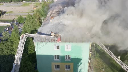 firemen : Nizhnevartovsk, Russia - July 1, 2019: firefighters extinguish a fire on the roof of a residential highrise building. top view.
