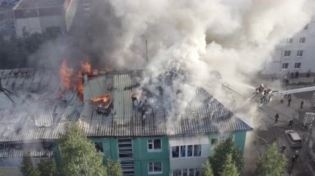 arson : Nizhnevartovsk, Russia - July 1, 2019: firefighters extinguish a fire on the roof of a residential highrise building. top view.