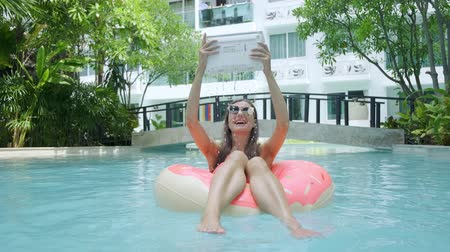 throws : female freelancer sits in an inflatable circle in the pool and throws the laptop into the water. Water flows from the laptop.