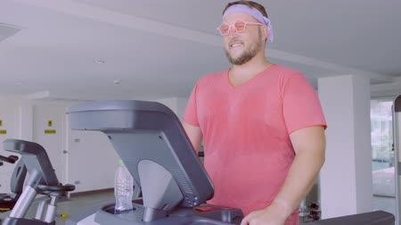 nerd : Funny fat male in pink glasses and in a pink t-shirt is engaged on a treadmill in the gym depicting a girl. 4k.