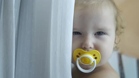 focus on : A cheerful little girl of 1 year old plays hide and seek behind the curtain, watching from behind the curtains, slow motion, 4k
