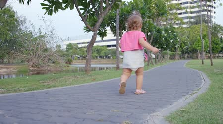 dances : Little girl 1 year old running along a path in the park among palm trees, slow motion, 4k