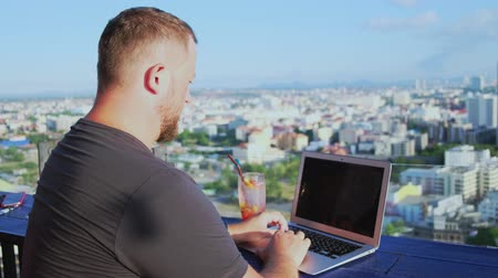 localização : Pattaya, Thailand - May 12, 2019: male working on a laptop in a cafe on the roof with a beautiful panoramic view. man drinking a cocktail and working on a computer