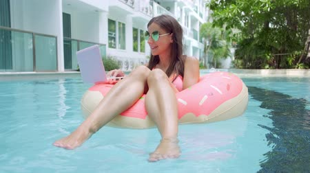 área de trabalho : female freelancer sits in an inflatable circle in the pool and drops the laptop into the water. Busy during the holidays. The concept of remote work. selective focus.