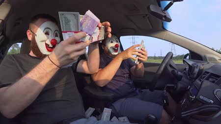 haydut : Two men in funny masks with guns in the car rejoice at money after a robbery. Armed robbers used weapons to rob money Stok Video