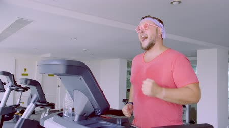 stripboek : Funny fat male in pink glasses and in a pink t-shirt is engaged on a treadmill in the gym depicting a girl. 4k.