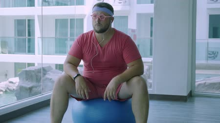 stripboek : Funny fat male in pink glasses and in a pink t-shirt is engaged on a fit ball in the gym depicting a girl. A wonderful man listens to music and dances on the ball in the gym