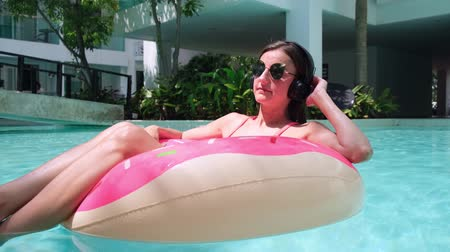 donas : Happy woman and inflatable swim ring in the shape of a donut in the pool and listens to music at the store Archivo de Video