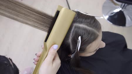 ondulação : Hairdresser does lamination and hair straightening in a beauty salon for a girl with brown hair. hair care concept. Vídeos