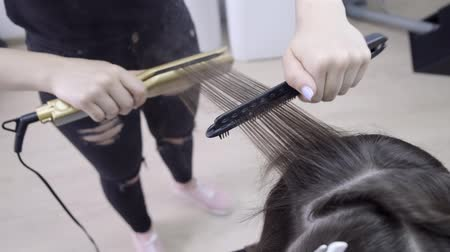 ondulação : hairdresser makes hair lamination in a beauty salon for a girl with brunette hair. hair care concept Vídeos