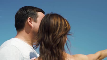 admirar : male and female couple look into the distance, admire the view against the blue sky, close-up. soft focus.