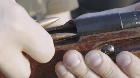 proiettili : Male fingers load the cartridge old rifle one by one.
