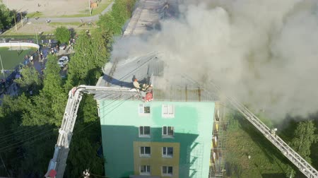 blussen : Nizhnevartovsk, Russia - July 1, 2019: firefighters extinguish a fire on the roof of a residential highrise building. top view.