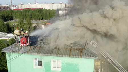 megelőzés : Nizhnevartovsk, Russia - July 1, 2019: firefighters extinguish a fire on the roof of a residential highrise building. top view.