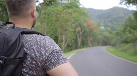 harcerz : Handsome tropical forest with a traveler young man with a backpack on the road to Thailand forest. A man walks on a tropical road and enjoys the views of nature.