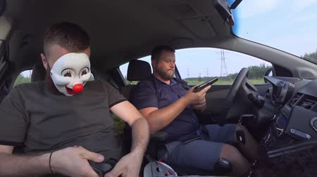 haydut : Two men in funny masks with weapons in the car preparing for the robbery. Armed robbers used weapons to rob money Stok Video