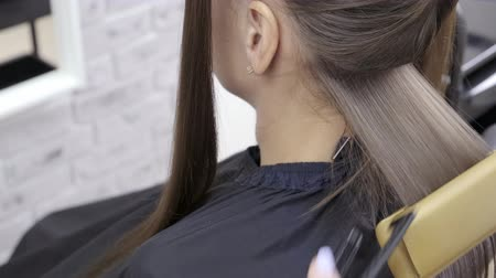 брюнет : Cute girl with long brunette hair hairdresser doing hair lamination in a beauty salon. concept of hair care treatment. Стоковые видеозаписи
