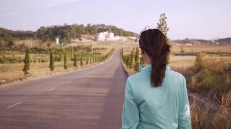 egyetlen virág : girl in a blue dress is walking among the fields and mountains. Girl walking along the road among fields and hills, back view