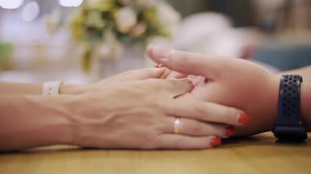 meghittség : Male hand touching female hand while romantic date in evening restaurant. Woman touching hand girlfriend on table at evening dinner in elegant cafe. Romantic people relationships