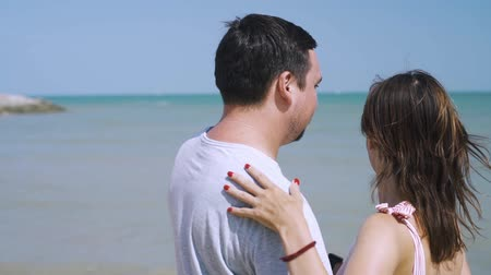 bağ : Happy young man and woman hugging on the beach, near a boat is tied, vacation concept. Stok Video
