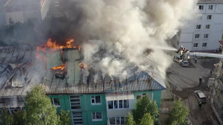 arson : firefighters extinguish a fire on the roof of a residential highrise building. top view.