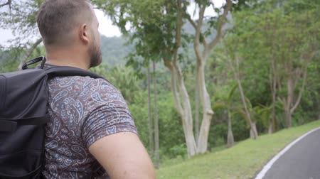přežití : Handsome tropical forest with a traveler young man with a backpack on the road to Thailand forest. A man walks on a tropical road and enjoys the views of nature.